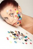 Beautiful woman with colorful buttons on her face leaning her head on white table full of various bu