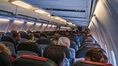 The Rear View Of The Many People On The Plane. Interior Of Airplane With Passengers, Sitting On Seat poster