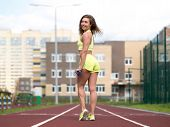 Female Urban Fitness. Caucasian Smiling Sexy Woman With Elastic Band Staying On Jogging Track Outdoo poster