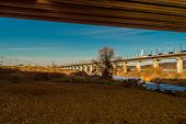 High Speed Train Traveling On Rail Bridge Over River Under Blue Sky. Train Slightly Blurred Due To S poster