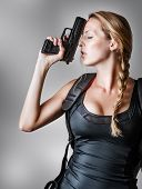 foto of handgun  - Young beautiful sexy blond Woman holding Handgun in hand - JPG