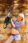 stock photo of chainsaw  - Sexy blonde girl builder with a chainsaw - JPG