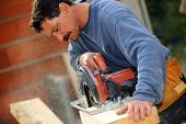 image of sawing  - Man cutting block of wood to size using circular saw - JPG