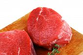 raw red meat : three fresh beef fillet chops with thyme twig on wooden plate . isolated over white b