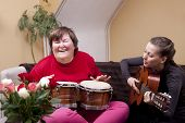 stock photo of bongo  - Two women make a music therapy and having fun - JPG