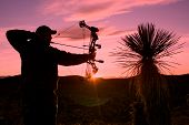 stock photo of archer  - a bowhunter silhouetted in a colorful sunrise - JPG