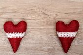 foto of bordure  - Two red hearts of cloth with bordure on old weathered wooden board - JPG