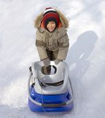 stock photo of ruddy-faced  - Funny little boy with sledge outdoors in winter - JPG