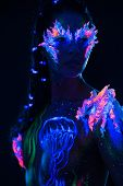stock photo of uv-light  - Beautiful woman with body art glowing in ultraviolet light - JPG