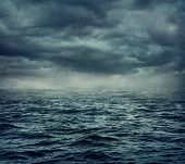 stock photo of rain clouds  - Rain over the stormy sea - JPG