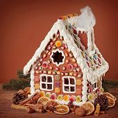 foto of gingerbread house  - Homemade gingerbread house on brown background - JPG