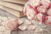 stock photo of rose bud  - Pink roses and old books on wooden desk - JPG