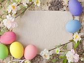 image of yellow buds  - Easter eggs and blank note on wooden background - JPG
