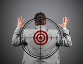 stock photo of crosshair  - Businessman surrendering with crosshair and target on his back - JPG