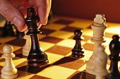 pic of chessboard  - Close up view of the hand of a man playing chess making a move holding the black king in his hand - JPG