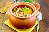 picture of pot roast  - Roast with chicken and potatoes in a clay pot a yellow napkin spoon crispbread pepper in the pot on a board - JPG