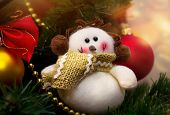 foto of ruddy-faced  - Funny snowman decoration in scarf on Christmas tree background - JPG