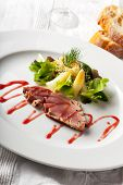 stock photo of yellowfin tuna  - grilled tuna steak on a plate with sauce - JPG
