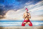 image of padmasana  - Christmas yoga in padmasana lotus pose by happy man in red trousers and Christmas hat on the beach near the ocean in India - JPG