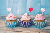 picture of cupcakes  - Photo of 3 cupcakes on wooden background - JPG
