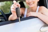 stock photo of rental agreement  - young smiling woman sitting in car taking key handover rent purchase - JPG