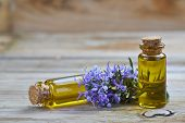 stock photo of small-flower  - Rosemary essential oil in a small glass vial and plant with flowers on a wooden background - JPG