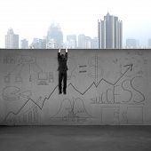 image of climbing wall  - Man climbing over wall with business doodles and city view background - JPG