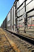 stock photo of railroad car  - A long string of railroad freight cars on a siding extend to a vanishing point