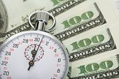 image of stopwatch  - Stopwatch and dollars. Time is money concept