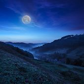 stock photo of moon-flower  - cold morning fog on a hillside meadow near mountain village at night in moon light - JPG