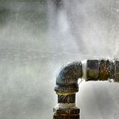 picture of leaked  - Old rusty pipe with leak and water spraying out - JPG