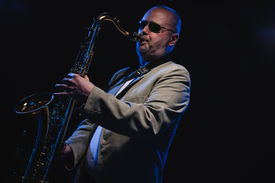 stock photo of saxophone player  - Adult musician playing tenor saxophone blue smoky background - JPG