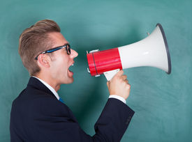 stock photo of shout  - Male Professor Shouting Though Megaphone Against Chalkboard - JPG