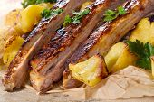 picture of ribs  - Prepared beef ribs in bbq sauce and baked potatoes - JPG