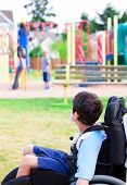 image of playground  - Disabled little boy in wheelchair sadly watching children play on playground - JPG