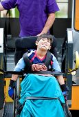 stock photo of handicap  - Happy disabled seven year old boy being transported on handicap school bus lift - JPG