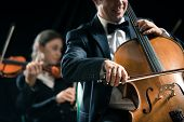 stock photo of orchestra  - Cello professional player with symphony orchestra performing in concert on background - JPG