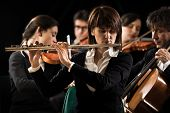image of orchestra  - Professional female flutist in concert with symphony orchestra players on background - JPG