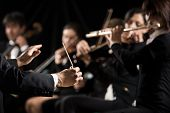 foto of conduction  - Conductor directing symphony orchestra with performers on background - JPG