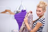 picture of dress mannequin  - Smiling fashion designer fixing dress on a mannequin - JPG