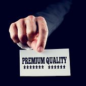 image of first class  - Businessman holding a card saying Premium Quality underlined with rows of stars conceptual of first - JPG