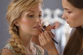 stock photo of cheer-up  - Make up artist doing professional make up of young woman - JPG