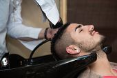 picture of beauty parlour  - Hairstylist Hairdresser Washing Customer Hair - Young Man Relaxing In Hairdressing Beauty Salon