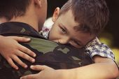 stock photo of say goodbye  - Boy and soldier in a military uniform say goodbye before a separation - JPG