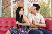 picture of hate  - Portrait of couple quarreling at home while sitting on sofa and looking with hate - JPG
