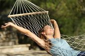 pic of rest-in-peace  - Happy woman relaxing on a hammock on holidays and raising arms in the mountain - JPG