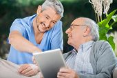 stock photo of male nurses  - Smiling male nurse assisting senior man in using tablet PC at nursing home porch - JPG