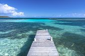 picture of extend  - Rustic wooden dock extends into clear shallow lagoon at Playa Larga beach on Caribbean island of Isla Culebra in Puerto Rico - JPG