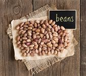 picture of pinto bean  - Pinto beans with small chalkboard on a wooden table - JPG
