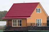 image of red siding  - Orange house with red roof and with white window - JPG